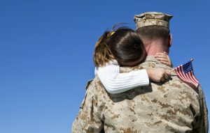 An image of young kid hugging her active duty dad - military marketing